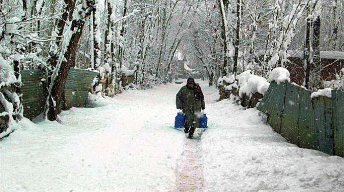 A milkman walks to distribute milk in a residential locality at Anantnag district in south Kashmir. (Photo: PTI)