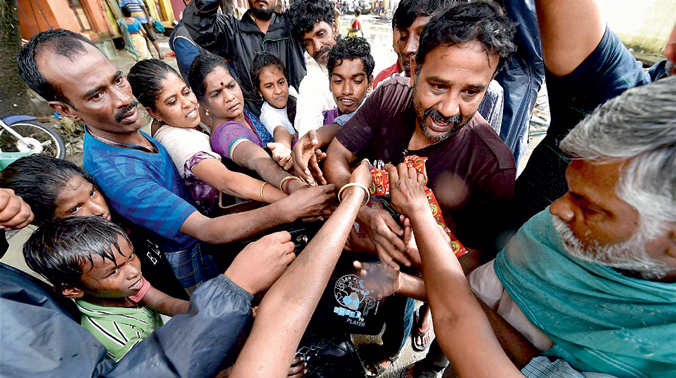 Volunteers distribute relief material to residents of Kotturpuram, one of the worst flood-hit localities in Chennai on Saturday. (Photo: PTI)