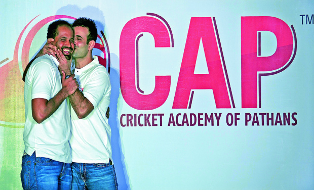 Indian cricketer Irfan Pathan (right) jokingly kisses his brother Yusuf Pathan during the launch event for the Cricket Academy of Pathans in Mumbai. (Photo: AFP)