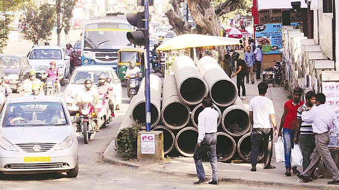 BWSSB has stocked big pipes on the footpath from Wind Tunnel road-ISRO junction to traffic junction near HAL Police Station on Old Airport Road, affecting the movement of pedestrians. (Photo: R. Samuel)