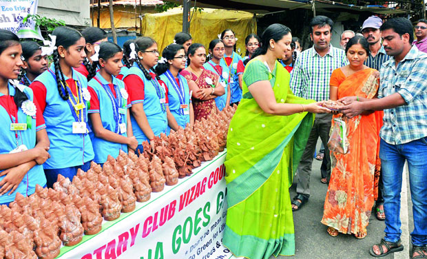 Students and a teacher distribute clay Ganesha idols under the agegis of Rotary Club Vizag at Sampath Vinayaka temple in Visakhapatnam on Wednesday. (Photo: DC)
