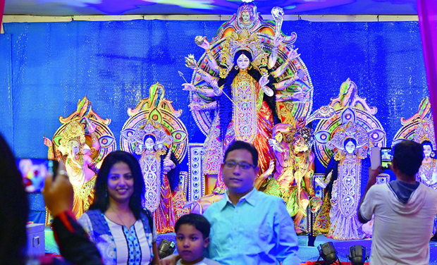 A family gets a photograph clicked in the backdrop of a Druga idol at the Banjara Function Hall on Sunday.  (Photo: DECCAN CHRONICLE)