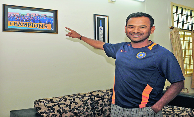 R. Sridhar, newly appointed fielding coach of the Indian cricket team, points to a frame of the Indian U-19 side he had coached to the U-19 World Cup win in 2012 in Australia that hangs on the wall of his house in Hyderabad in this file photo. (