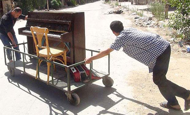 A file picture showing Aeham al-Ahmad, being helped by a friend to push his piano along a the street in the southern Damascus suburb. (Photo: AFP)