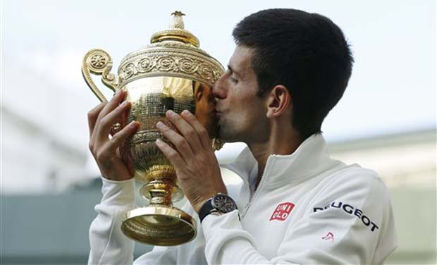 Novak Djokovic of Serbia kisses the trophy after defeating Roger Federer of Switzerland in the men's singles final match at the All England Lawn Tennis Championships in Wimbledon. Photo: AP