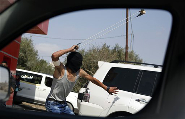 A Palestinian uses a slingshot during clashes following a demonstration in the West Bank city of Ramallah. (Photo: AP)