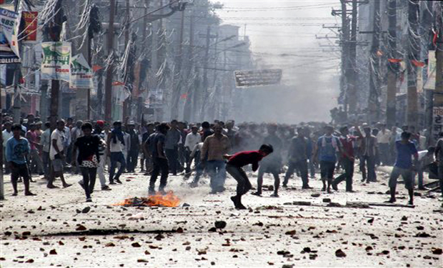 Ethnic Madhesi protesters throw stones and bricks at Nepalese policemen in Birgunj, a town on the border with India, Nepal, Monday, Nov. 2, 2015. Ethnic protesters demonstrating against the new constitution clashed with police in south Nepal Monday