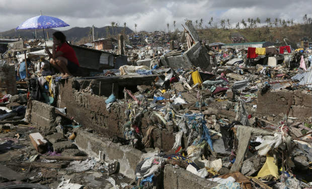 A survivor sits among debris in the typhoon ravaged city of Tacloban, Leyte province, central Philippines on Wednesday. -AP
