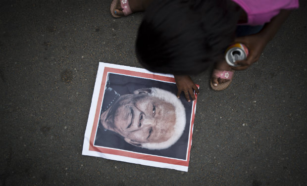 A girl picks up a poster showing the face of Nelson Mandela after it fell to the ground, as she and others celebrate his life, in the street outside his old house in Soweto, Johannesburg. -AP