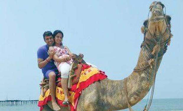 A couple enjoys a camel ride on Alappuzha beach