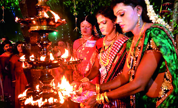 Men dressed as women light lamps in front of the deity
