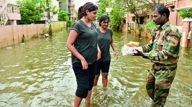 Two girls collect relief material from an Army jawan in Velachery, one of the worst flood-hit areas in Chennai (Photo: PTI)