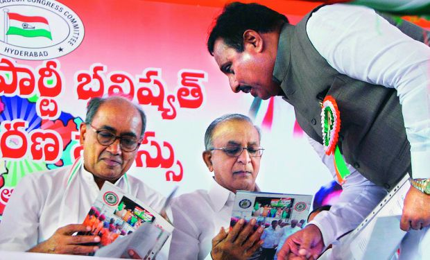 Telangana state Congress leader Danam Nagender has a word with AICC general secretary Digvijay Singh as the latter and former Union minister S. Jaipal Reddy go through a booklet at the Telangana PCC workshop in Hyderabad on Monday. (Photo: DC)