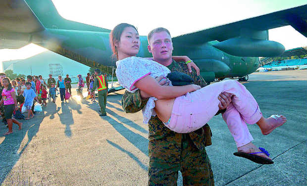 A US Marine carries an injured woman who survived the Super Typhoon Haiyan in the central coastal city of Tacloban, as they disembark from a military cargo plane on Tuesday. The UN launched an appeal for a third of a billion dollars on November 12