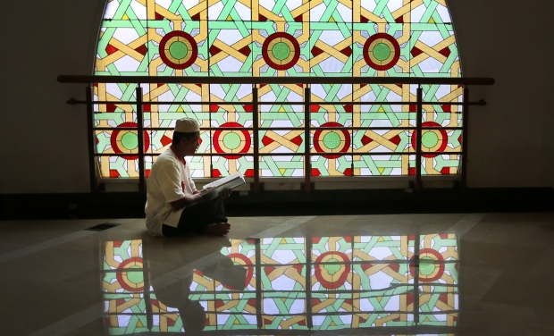 An Muslim man reads the holy book of Quran at a mosque during the second week of Ramadan in Jakarta (Photo: AP)