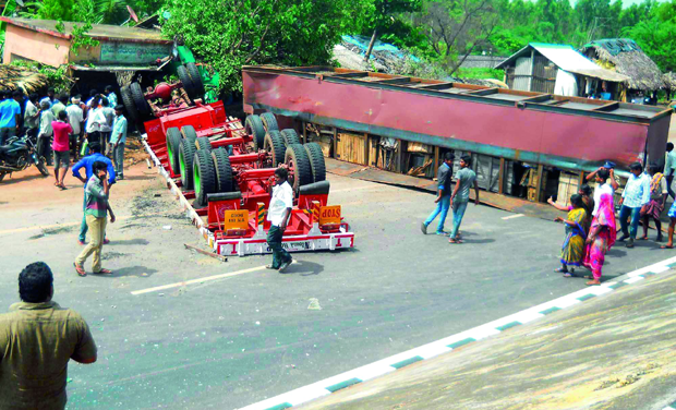 A lorry overturned after ramming into elevated median of the road at Bhimadole in West Godavari on Tuesday.