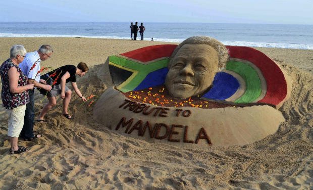 Tourists offer floral tributes near a sand sculpture of Nelson Mandela on a beach in Puri, Odisha on Friday - AP