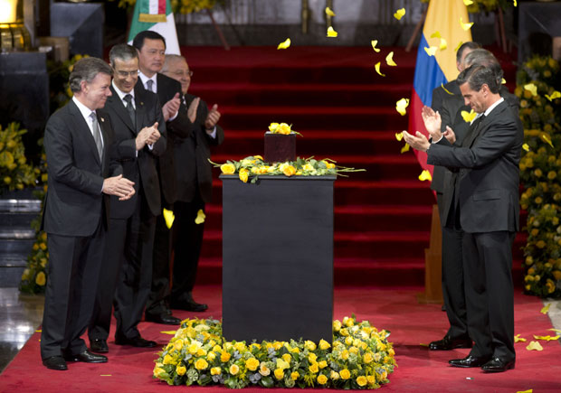 Columbia's President Juan Manuel Santos, left, and Mexico's President Enrique Pena Nieto, right, applaud as yellow paper butterflies fall, next to the urn containing the ashes of Colombian Nobel Literature laureate Gabriel Garcia Marquez during the