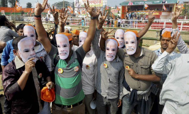 Supporters of BJP Prime Ministerial candidate Narendra Modi, seen wearing his masks, during the leader's Naba Chetana Rally in Agartala on Saturday - PTI