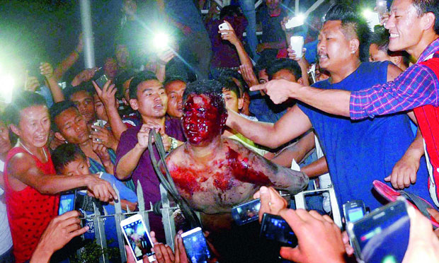 Protesters beat an accused, centre, of raping a woman after being dragged out of district jail in Dimapur, Nagaland on Thursday. (Photo: PTI)