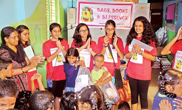 Nikhiya Shamsher (3rd R) distributing bags, books and stationery to the underprivileged