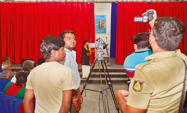 A police officer shoots video while the Kabhir Kala Manch from Pune performs at St. Aloysius College on Friday (Photo: DC/File)