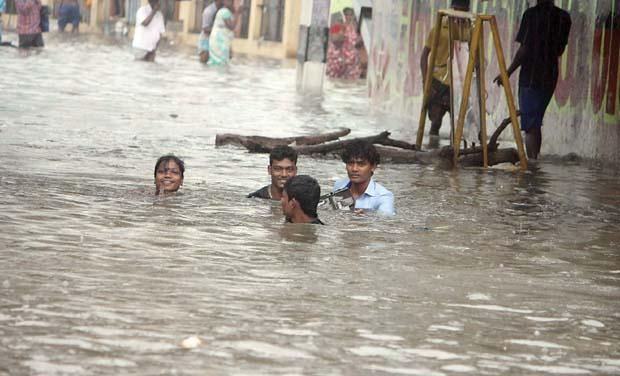 People wade through neck-deep rain water in Perambur on Friday. (Photo: DC)