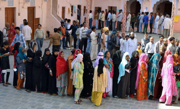 People queue up at a polling booth to caste their vote during the state assembly elections in Ajmer on Sunday. -PTI