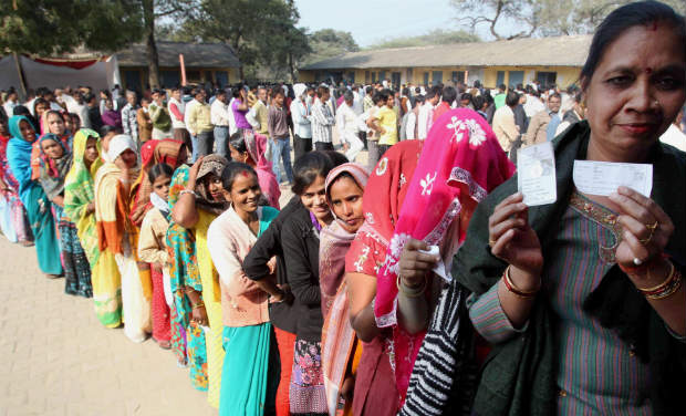 Women wait in a queue to cast their votes for Delhi Assembly elections, at a polling station at Badarpur in New Delhi on Wednesday. PTI