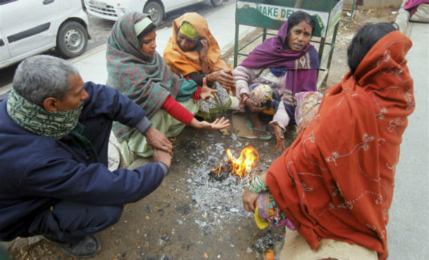 People warm themselves in front of a bonfire during a cold day in New Delhi. PTI