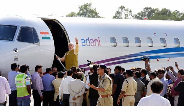 Prime Minister-designate Narendra Modi waves while boarding a flight for Delhi at the airport in Ahmedabad (Photo: PTI)