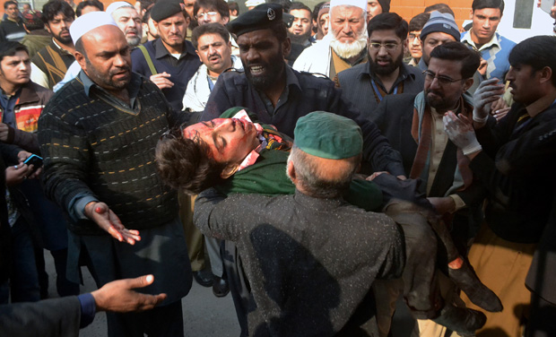 Hospital security guards carry a students injured in the shootout at a school under attacked by Taliban gunmen in Peshawar, Pakistan (Photo: AP)