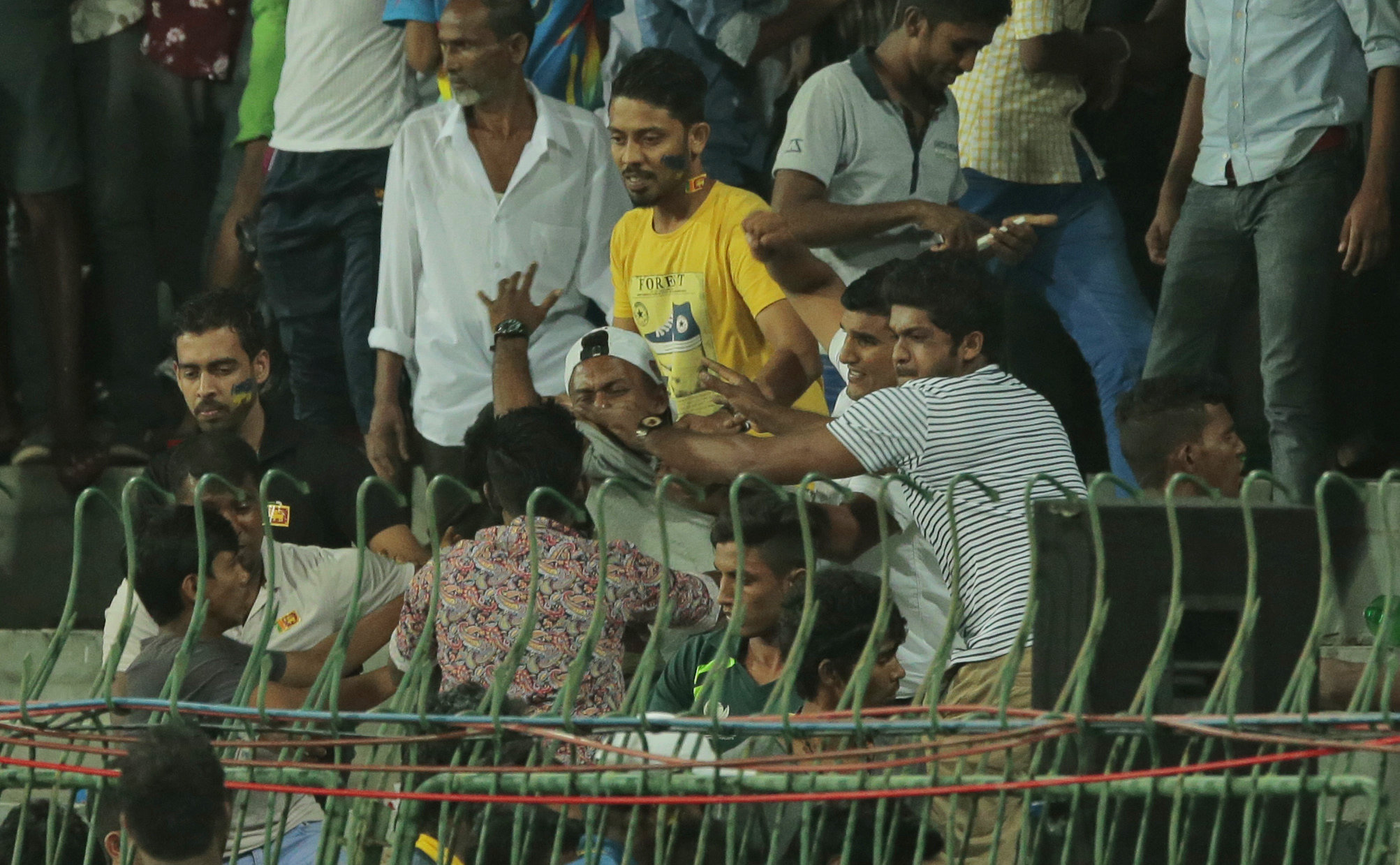 Rioting crowds forced cricketers to retreat to their dressing rooms as projectiles reached the outer field of the Premadasa Stadium during the third one-day international between Pakistan and hosts Sri Lanka on Sunday. (Photo: AP)