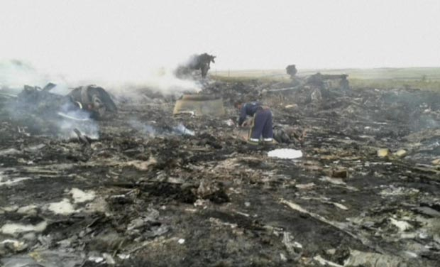 In this image taken from video, people walk on the debris at the crash site after a passenger plan was shot down as it flew over Ukraine, near the village of Hrabove, in eastern Ukraine (Photo: AP)