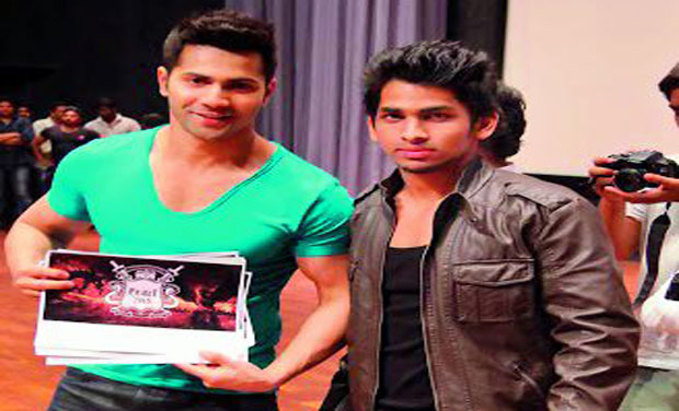 Varun Dhawan poses with a student and also a poster of their upcoming fest