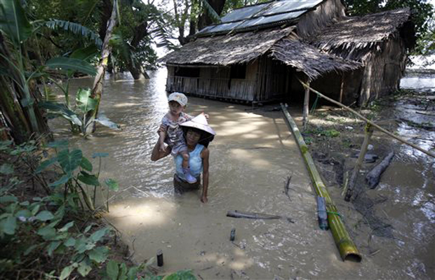 A woman carrying her child wades through floodwaters near a half-submerged residence in Hinthada township, Ayeyarwaddy delta, Myanmar. The number of people affected by flooding across Myanmar was approaching 1 million on Sunday, with waters in the
