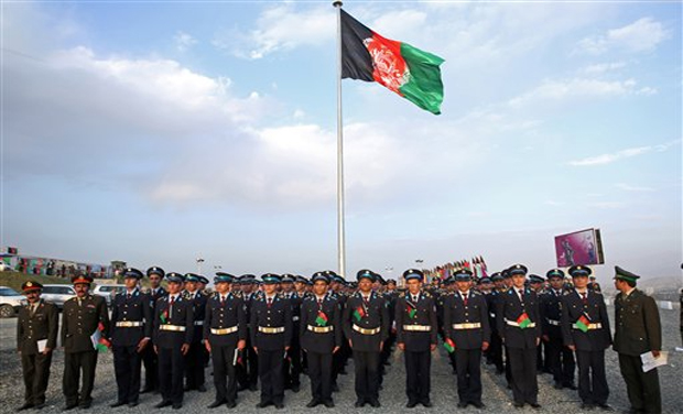 Afghanistan's military academy students stand guard in front of the largest ever Afghan flag to fly
