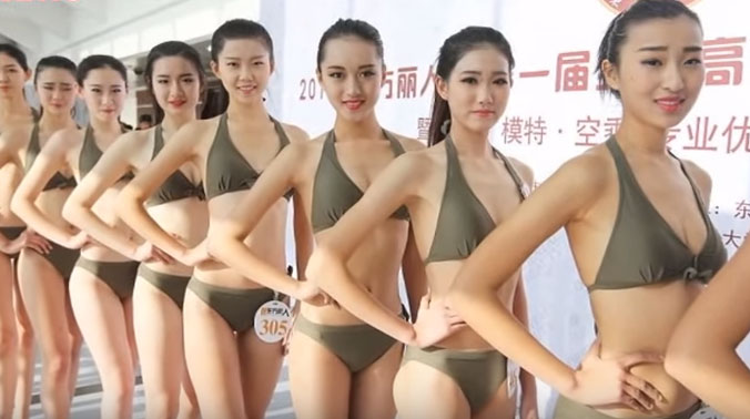 0a6bd63c719 Screen grab featuring high school graduates in China parading in bikinis to  bag jobs as models