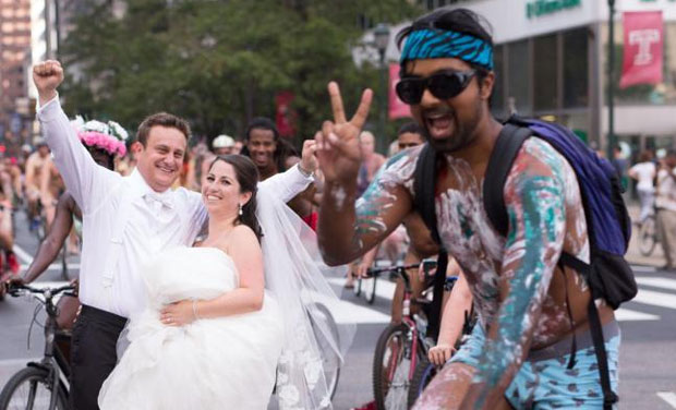 Ross Cohen, left, and Blair Delson celebrate their wedding day at the edge of Dilworth Plaza in Philadelphia, as participants in the annual Philly Naked Bike Ride pass by. (AP)