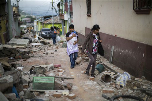 A Family walks trough a street littered with the rubble from buildings that fell during an earthquake in San Pedro, Guatemala, on Monday. (Photo: AP)