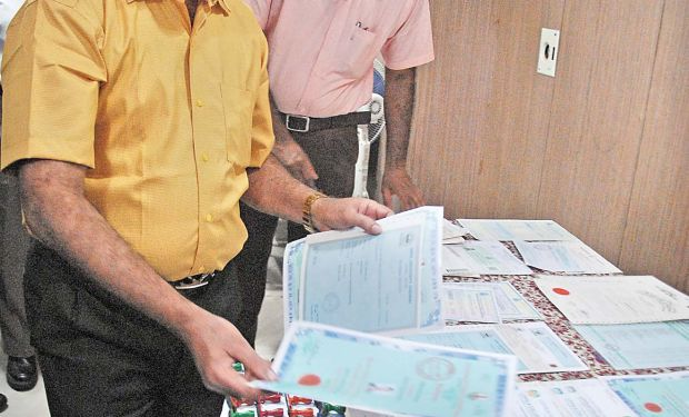 central crime branch ccb officials inspecting the certificates and rubber stamps seized from the