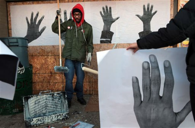 St. Louis artist Damon Davis hangs his photographs of hands to cover the plywood-covered windows at the Ferguson Market on Wednesday, in Ferguson, Missouri. (Photo: AP)