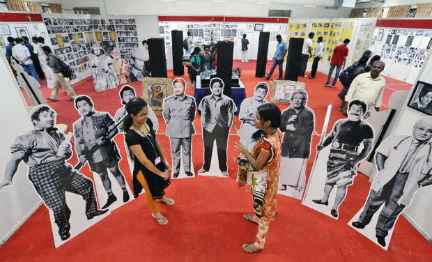 Students cheerfully take pictures with cutouts of thespian Sivaji Ganesan from the film Navarathri.