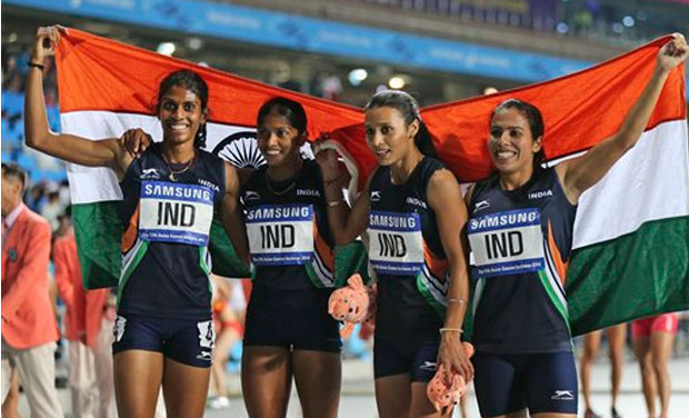 Indian team members celebrate with the national fag after finishing first in the women's 4 x 400m relay final at the 17th Asian Games in Incheon, South Korea, Thursday, Oct. 2, 2014.(Photo: AP)