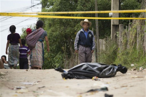 A resident pauses to look at a taped off area, where a body lies wrapped in a black bag, in Pajoques, Guatemala, on Saturday. (Photo: AP)