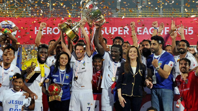 Fatorda: Chennaiyin FC players celebrate with the winning trophy after defeating FC Goa by 3-2 in the finals of the 2nd edition of the ISL at Fatorda in Goa on Sunday. Nita Ambani and Actor Abhishek Bachchan are also seen. (Photo: AP)