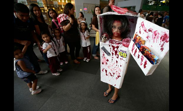 Children look at Ashley Perez 10 dressed in her scary costume as she takes & Halloween Celebrations