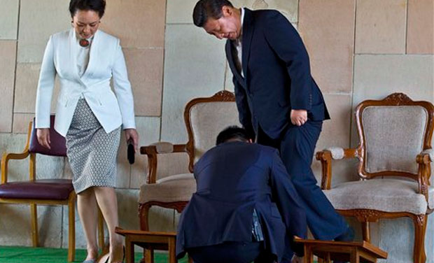 An aide helps Chinese President Xi Jinping wear his shoe, with his wife Peng Liyuan standing beside, after visiting Rajghat in New Delhi (Photo: AP)