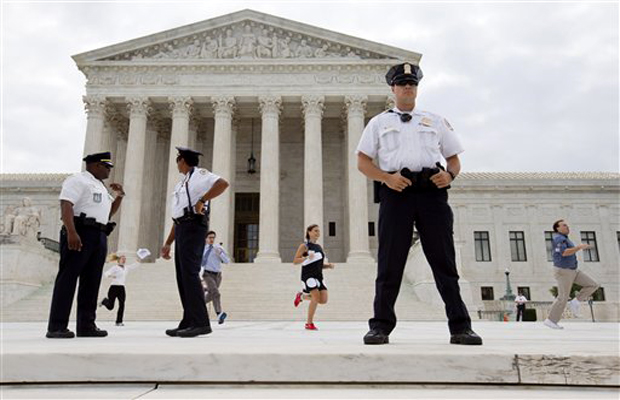 Interns run behind a line of security outside of the Supreme Court in Washington, Friday June 26, 2015, to reveal the court's decision declaring that same-sex couples have a right to marry anywhere in the US (Photo: AP)