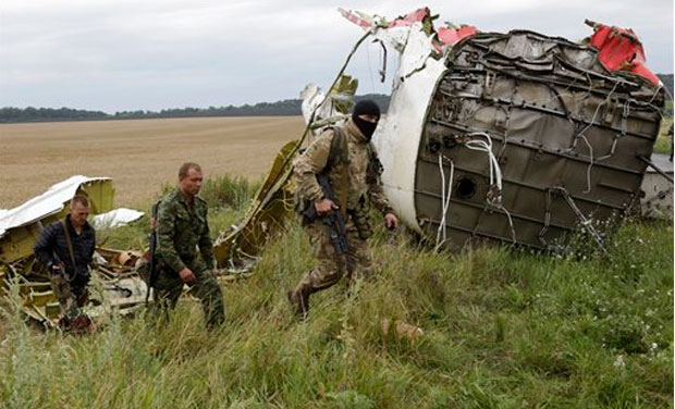 Pro-Russian fighters walk at the site of a crashed Malaysia Airlines passenger plane near the village of Hrabove, Ukraine, eastern Ukraine Friday, July 18, 2014. Rescue workers, policemen and even off-duty coal miners were combing a sprawling area